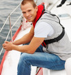 Happy young man wearing a life jacket in a sail boat at sea